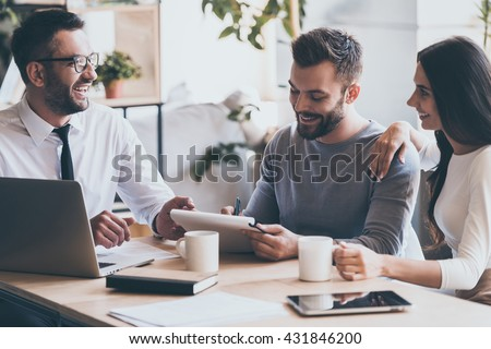 Just put your signature here! Cheerful young man signing some documents while sitting together with his wife and man in shirt and tie  - stock photo