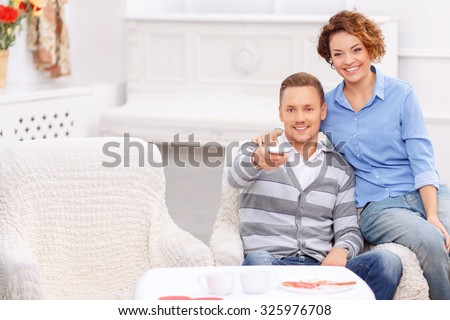 Just relax. Pleasant jubilant young couple sitting in the armchair and  watching TV while bonding to each other