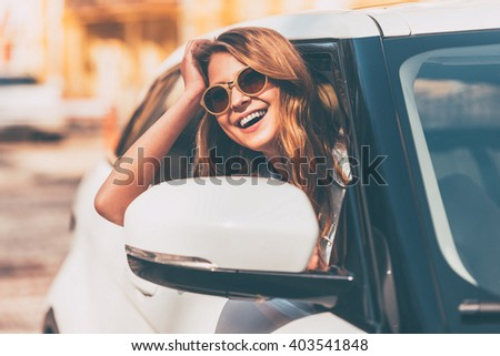 Just road ahead. Beautiful young cheerful women looking at camera with smile while sitting in her car - stock photo