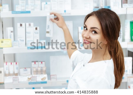 Just what you need. Close up shot of a professional pharmacist checking stock in an aisle of a local drugstore smiling looking over her shoulder to the camera. - stock photo