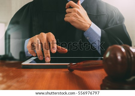 justice and law concept.Male judge in a courtroom with the gavel,working with digital tablet computer on wood table,filter effect