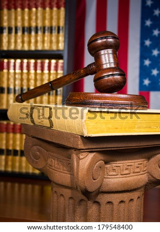 Justice Gavel on Greek Column with blurred law books in the background - stock photo