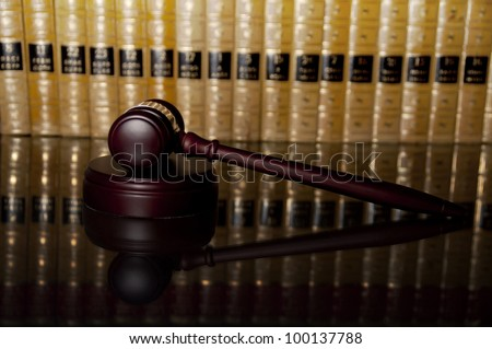 Justice gavel with reflection on glass table with law books in the background - stock photo