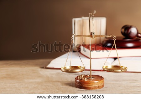 Justice scales with wooden gavel and books on brown background - stock photo