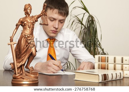 Justice statue and lawyer reading a book in the office - stock photo