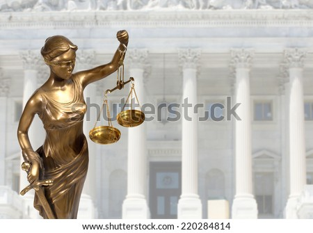 Justice statue is on against the courthouse  - stock photo