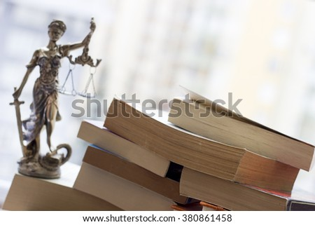 Justice statue with sword and scale and books. Law concept - stock photo