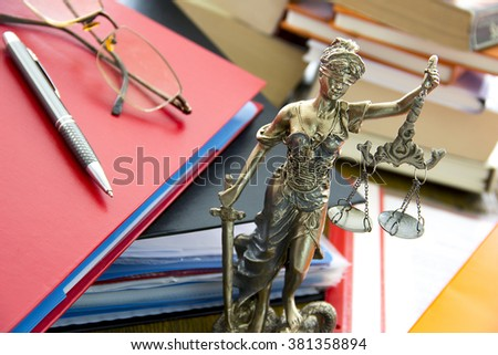 Justice statue with sword and scale, folders and books. Law concept - stock photo