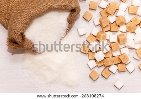 Jute bag full of sugar and sugar cubes - stock photo