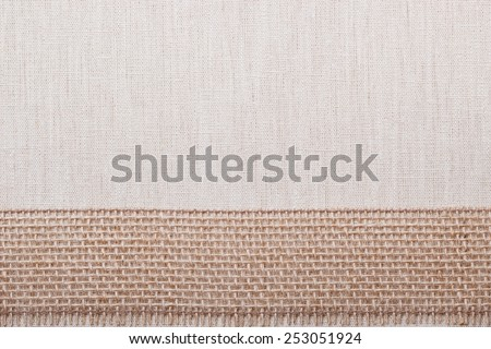 Jute bagging ribbon on bright fabric textile material, natural linen background - stock photo