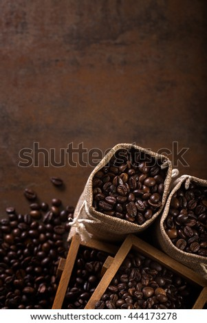 Jute bags and wooden containers filled with cofee beans on the rust background. Low light. - stock photo