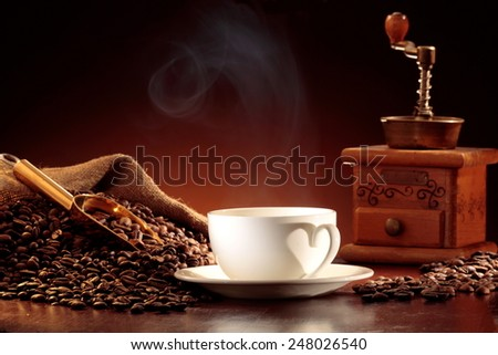 Jute sack of coffee beans with a golden scoop, coffee mill and a steaming cup of coffee - stock photo