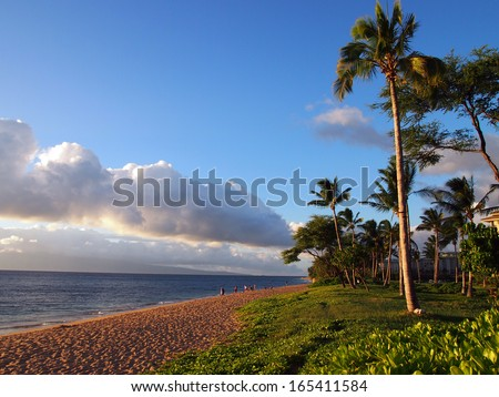 Kaanapali Beach at Dusk with gentle waves, people, hotels and trees. Island of Lanai can be seen in the distance on Maui, Hawaii. - stock photo