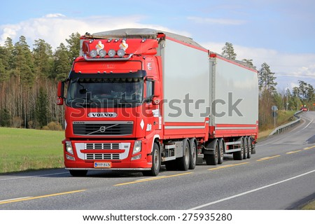 KAARINA, FINLAND - MAY 2, 2014: Red Volvo FH full trailer truck on highway. The Volvo I-See can save up to 5% of fuel during a driving cycle. - stock photo