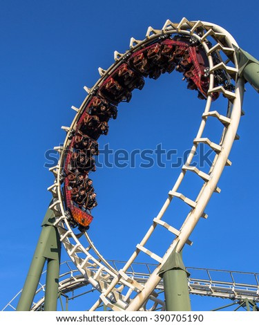 KAATSHEUVEL/THE NETHERLANDS - OCTOBER 31th, 2015: People enjoying an exhilerating rollercoaster ride at a theme park against blue sky - stock photo