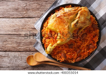 Kabsa of chicken with rice and vegetables on a plate on the table. horizontal view from above