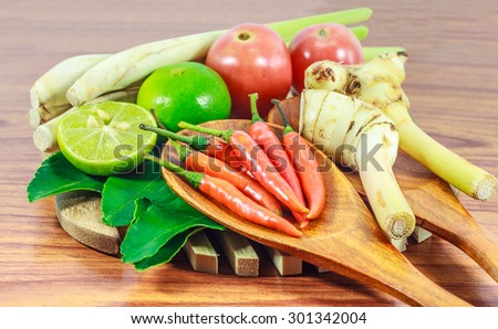 kaffir lime leaf, lemon, lemongrass, galangal, tomatoes , chili, herb and spicy ingredients for making Thai food on wood background. - stock photo