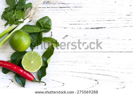 Kaffir lime leaves, fruit, coriander or cilantro, red chilli and green onions over white distressed wooden background. Overhead view.