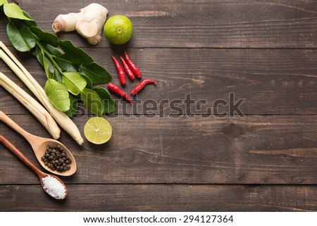 Kaffir lime leaves, Ginger, lemon, Pepper, Salt,  Red chilli and Green onions on wooden background. Overhead view.  - stock photo