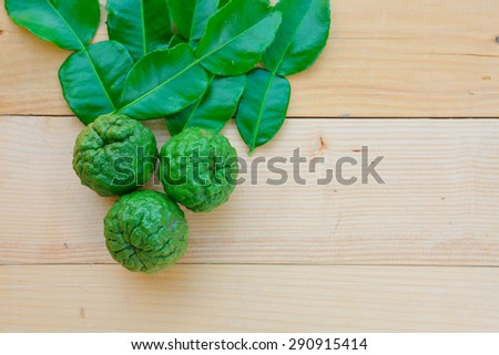 kaffir lime with leaf on wooden board - stock photo