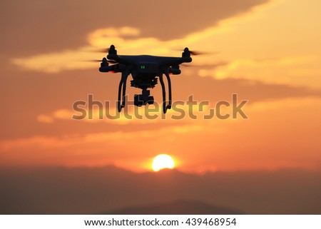 KAGAWA, JAPAN - JUNE 19, 2016: Remote controlled drone Dji Phantom 3 equipped with high resolution video camera hovering in air and sunset.  - stock photo