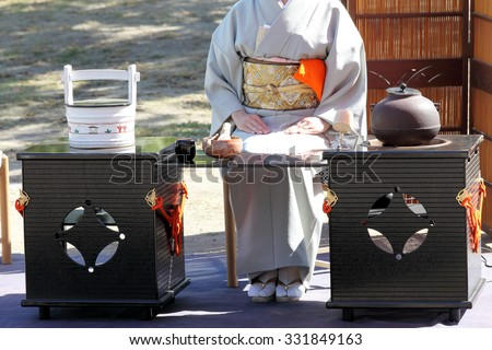 KAGAWA, JAPAN - OCTOBER 25, 2015: Japanese woman in traditional kimono prepares the tea ceremony at garden of the Marugame-castle on October 25, 2015 in Kagawa Japan.