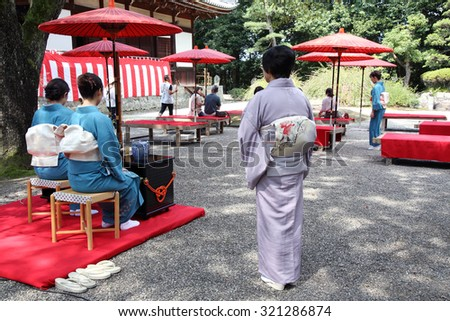 KAGAWA, JAPAN - SEPTEMBER 20, 2015: Japanese women in traditional kimono prepares the tea ceremony at garden of the Hagiwara Temple on September 20, 2015 in Kagawa Japan. - stock photo