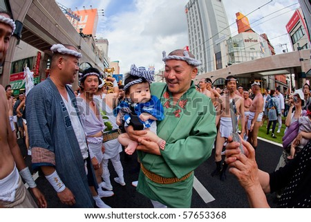 KAGOSHIMA CITY, JAPAN - JULY 19: Japanese man holding his baby at the Ogion festival July 19, 2009, in Kagoshima City, Japan.