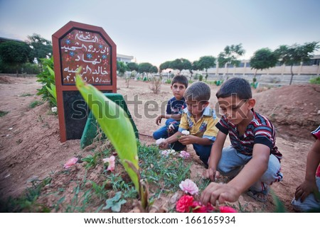 KAHNSHEIKHOUN, SYRIA,  JUNE 20 2013:  children lay flowers on grave of friends, killed by Bashar Al Assad forces. - stock photo