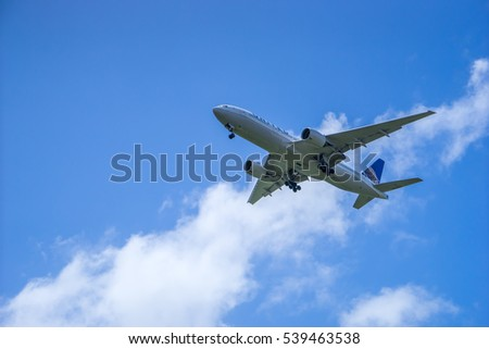 Kahului, USA, April 9, 2014: Landing plane in Kahului Airport on blue sky and white clouds background