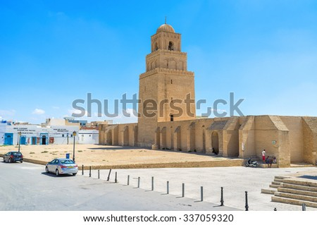 KAIROUAN, TUNISIA - AUGUST 30, 2015: The medieval Grand Mosque looks like the defensive fortress with a high ramparts, huge minaret and large courtyard, on August 30 in Kairouan.