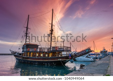 KALAMATA, GREECE - MARCH 2018: Scenic sunset at the port of Kalamata city with many traditional wooden fishing boats along the coast. Kalamata, Messenia, Greece