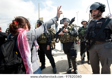 KALANDIA, OCCUPIED PALESTINIAN TERRITORIES - MARCH 8: A Palestinian woman confronts Israeli soldiers at the Kalandia checkpoint during protests against the occupation of Palestine on March 8, 2012. - stock photo