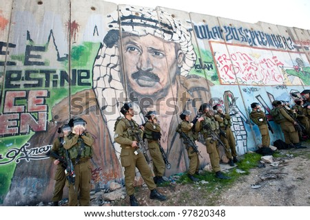 KALANDIA, OCCUPIED PALESTINIAN TERRITORIES - MARCH 8: Israeli soldiers are overcome by the effects of their own tear gas during protests against the occupation of Palestine on March 8, 2012. - stock photo