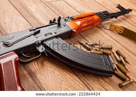 Kalashnikov assault rifles with ammunition on a wooden table - stock photo