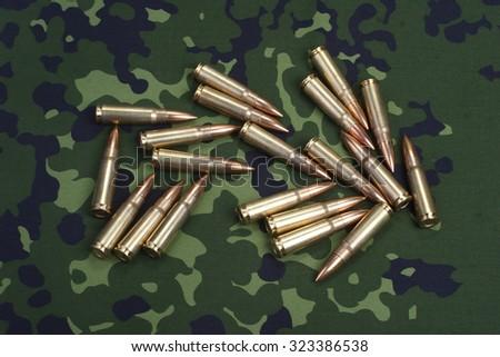 kalashnikov cartridges on camoflaged background - stock photo