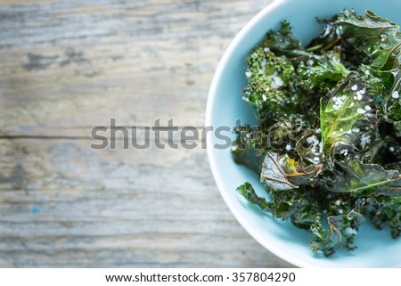 Kale chips with salt in pastel blue bowl captured from above (top view). Healthy dietetic snack. Vintage rustic wood as background. Background layout with free text space. - stock photo