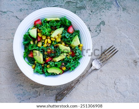 Kale, corn and avocado salad on rustic stone background - stock photo