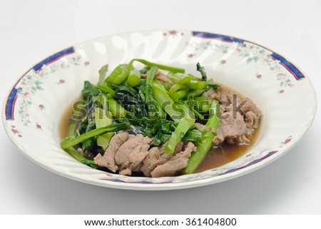 Kale fried in Oyster sauce with pork (famous thai food) - stock photo