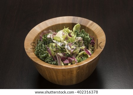 Kale salad in a wooden bowl/Kale Salad/Wooden bowl holds nutritious salad  - stock photo