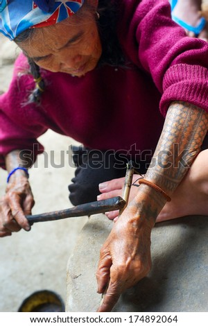 KALINGA, PHILIPPINES - MARCH 29, 2012: Unidentified woman makes traditional Cordillerans tattooing . Indigenous groups in Philippines have been practising the art of tattooing for centuries - stock photo