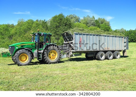 KALININGRAD REGION, RUSSIA - JUNE 11, 2015: John Deere 7930 tractor with tipper semitrailer Fliegl Gigant ASW 393 with the collected a forage for cows - stock photo