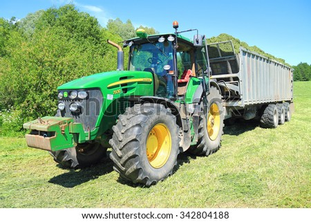 KALININGRAD REGION, RUSSIA - JUNE 11, 2015: The John Deere 7930 tractor with the dumping Fliegl Gigant ASW 393 semi-trailer in the field in a sunny day - stock photo