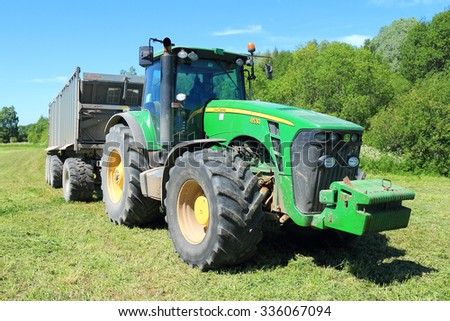 KALININGRAD REGION, RUSSIA - JUNE 11, 2015: The wheel John Deere 8530 tractor with the trailer in the field at the wood - stock photo