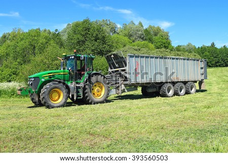 KALININGRAD REGION, RUSSIA - JUNE 11, 2015: The wheel John Deere 7930 tractor with the trailer with a mowed grass in the field