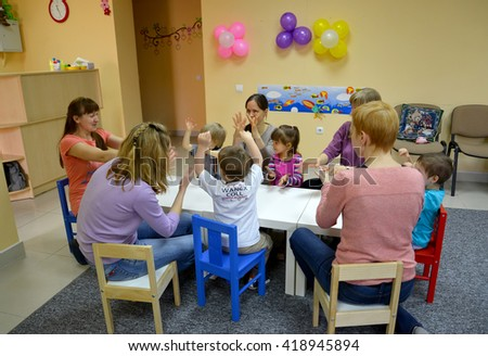 KALININGRAD, RUSSIA - APRIL 17, 2014: Joint game of children with parents at a table. Studio of creative development