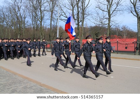 KALININGRAD, RUSSIA - APRIL 2, 2016: Police officers go a ceremonial step with national flag down the street of the city of Kaliningrad