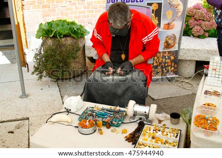 Kaliningrad, Russia - August 3, 2016: Craftsman makes and sells jewelry made of amber near Museum of Amber in Kaliningrad