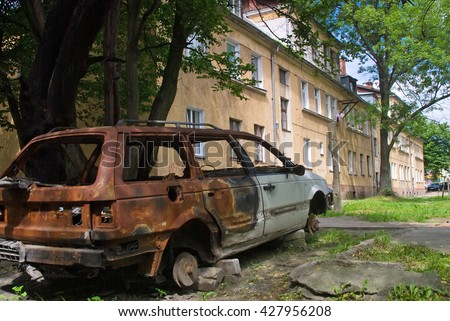 Kaliningrad, Russia - July 1, 2010: Burned-down car standing in yard of residental house - stock photo