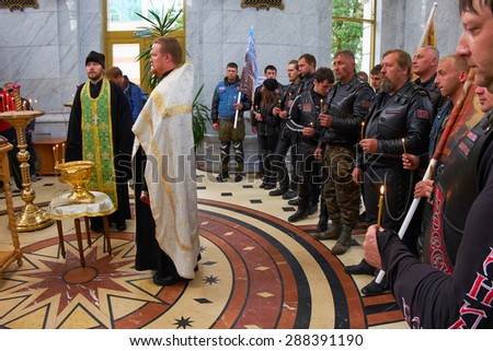 KALININGRAD, RUSSIA - JUNE 17, 2015: The Church of Peter and Fevronia. Prayer for the Day of memory and grief, beginning of the WW II. First in Kaliningrad procession on motorcycles and priest - stock photo